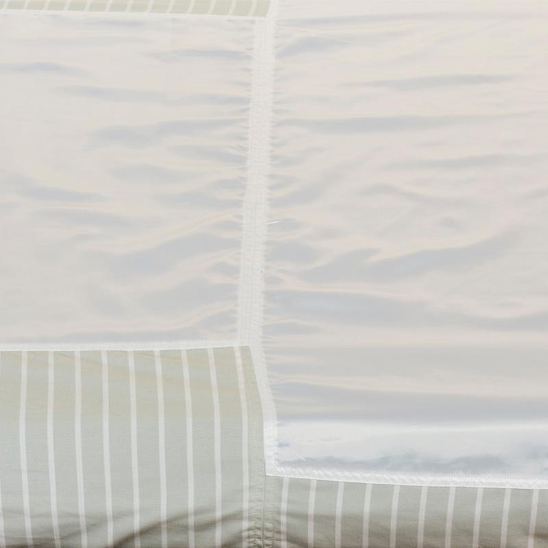 Slide sheets are made onto a bed. The main part of the image shows their shiny white surface, while the bottom of the image is the green and white vertical stripes of the fabric that folds under the bed when it is made.