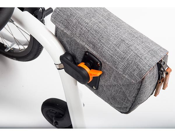 The Kinetic Balance Rack Pack, a grey bag, clipped to the frame of a white manual wheelchair.