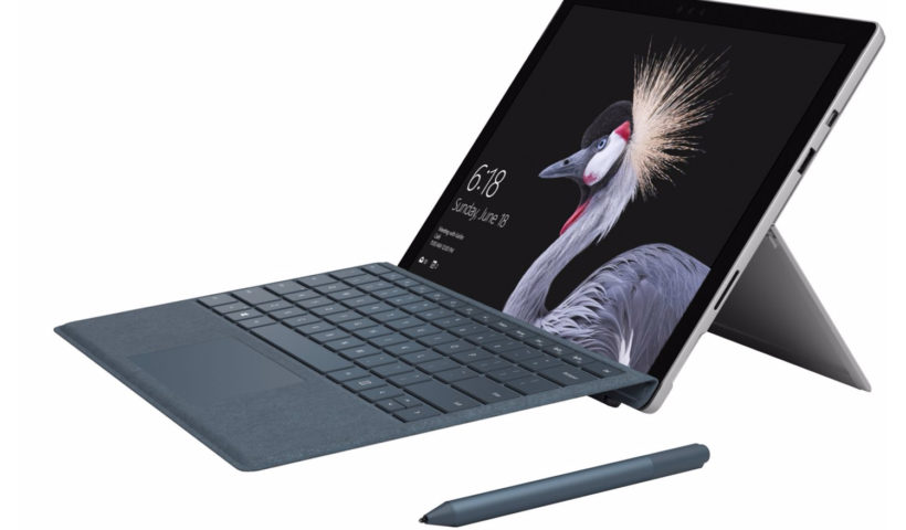 A laptop, with a very thin keyboard and a metal kickstand. There is a bird on the screen. There is a pen in front of the laptop.