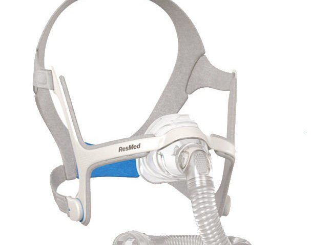 A breathing mask, as if worn by an invisible head. The headgear is stretched as if round a head, with the mask covering where the nose would be. A tube curves from the nose to coil below the image.