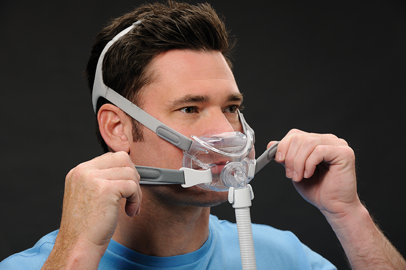 The head and shoulders of a white man with dark hair in a blue t-shirt. Over his mouth is a breathing mask which runs below his nose. There are straps across his head, and he is pulling straps either side of his face tighter.